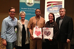 Helping Hands $500 Student Grant Presentation at the American Massage Conference in Atlanta. L-R - Scott Dartnall, AMC; CG Funk, Massage Envy; Roderick Howard, student winner; Camille Wiley, student winner; Marshall Dahneke, Performance Health.