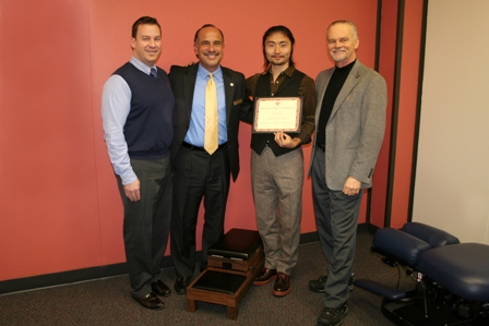 Dean of Clinics Adam Morrell, DC; President Edwin Cordero, DC; Hirofumi Isobe; and VP for Academic Affairs Bob Irwin, DC, with the black walnut knee chest adjusting table.