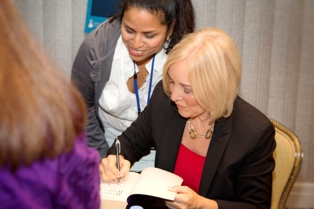 Presenter Christiane Northrup, MD, signs a copy of her New York Times bestselling book at the Metagenics Lifestyle Summit.