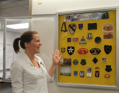 NUHS intern Jordan Anton recounts the patients and stories represented by each piece of memorabilia on the Veterans Display at National University's PTSD Clinic.